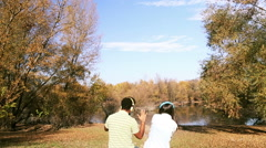 Man and woman listening to music using headphones while sitting by lake Stock Footage