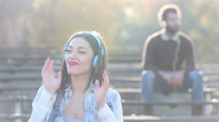 Woman listening to music on headphones, man blurred in background - stock footage