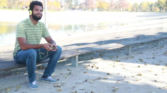 Handsome man with headphones listening to music on smartphone at park - stock footage