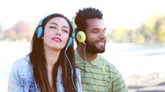 Couple with headphones listening to music and dancing to the rhythm Stock Footage