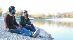 Cute couple sitting by lake and listening to music with headphones Stock Footage