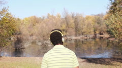 Back view of man with headphones listening to music by the lake Stock Footage