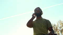 Young african american man with headphones listening to music at park - stock footage