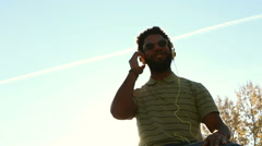 Young african american man with headphones listening to music at park Stock Footage