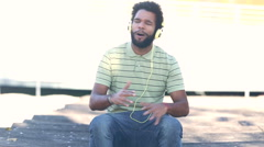 african american man with headphones listening to music and singing - stock footage