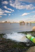 Long exposure shot of a wastewater pipe and a large oil refinery in the harbo Stock Photos