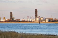 Raised lift bridges and industry in the harbor of Antwerp, Belgium with warm  Stock Photos