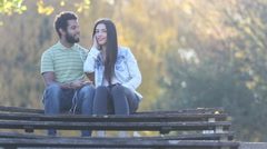 Man kissing woman on a cheek while they listening to music on earphones - stock footage