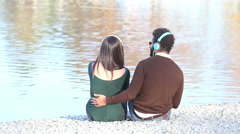 Couple listening to music with headphones, sitting by lake Stock Footage