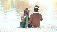 Couple in love sitting by lake and listening to music with headphones Stock Footage