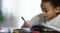 Young girl enjoying her colouring in book Stock Footage