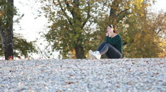 Woman listening to music with headphones and sending kiss to camera - stock footage