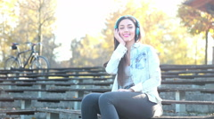 Beautiful woman listening to music with headphones at the park Stock Footage