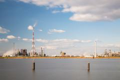 Long exposure shot of a refinery with tall flare stack in the port of Antwerp - stock photo