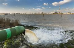 A wastewater pipe and a large oil refinery in the harbor of Antwerp, Belgium  - stock photo