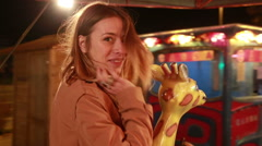 Beautiful woman having fun riding carousel in amusement park Stock Footage