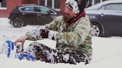man takes off his gloves sitting on snow - stock footage