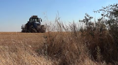 High capacity tractor plow a field on which was harvested wheat 01 Stock Footage