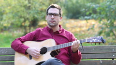Man playing acoustic guitar and singing in park - stock footage