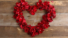 Wind blows red rose petals in Heart shape on wood background. - stock footage