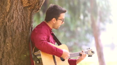 Man playing acoustic guitar leaning against a tree - stock footage