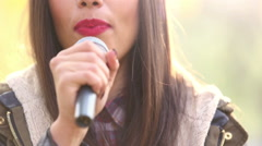 View of woman's mouth with red lipstick, smiling and singing with microphone - stock footage