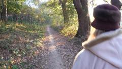 Women walk in an alley of the park in a fall cold day lit the sun at sunset Stock Footage