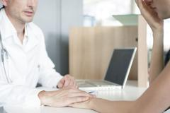 Stock Photo of Doctor consoling patient after delivering bad news, cropped