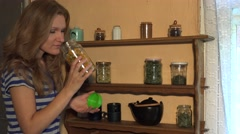 Young herbalist woman pick dried herbs from glass jar in rural house. 4K Stock Footage