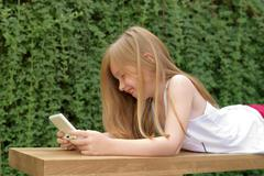 Stock Photo of Girl lying on stomach outdoors, playing handheld video game