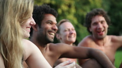 Four friends laughing while sitting in nature Stock Footage