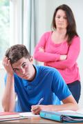 Frustrated Mother Watching Son Doing Homework Stock Photos