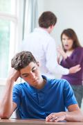 Unhappy Teenage Boy With Parents Arguing In Background - stock photo