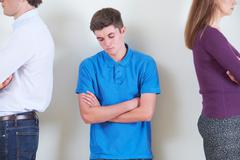 Teenage Boy Standing Between Parents Who Are Ignoring Each Other Stock Photos