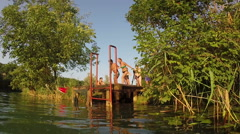 Young man and woman holding hands while jumping into river Stock Footage