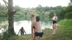 Friends having fun jumping off rope swing into river Stock Footage