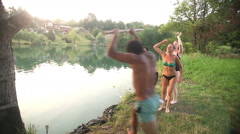 Man jumping off rope swing into river while friends cheer for him - stock footage