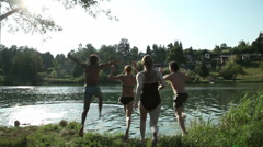Four young friends jumping into river Stock Footage