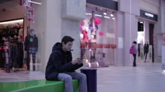 Teen on a bench and playing phone Stock Footage