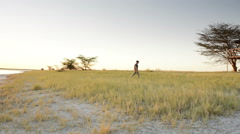 Man Walking in Africa at Sunset Stock Footage