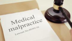 Medical malpractice lawsuit documents with gavel placed on desk of judge in c Stock Footage