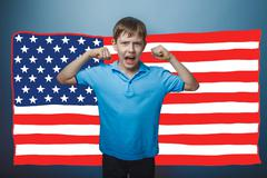 Adolescent the boy screaming showing strength hands American fla Stock Photos