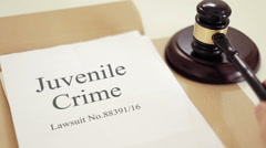 Juvenile offending lawsuit verdict folder with gavel placed on desk of judge Stock Footage