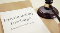 Discriminatory Discharge lawsuit verdict folder with gavel placed on desk of Stock Footage