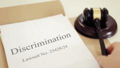Discrimination lawsuit verdict folder with gavel placed on desk of judge in c - stock footage