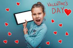 Girl points a finger to the tablet and yells Valentine's Day cel - stock photo