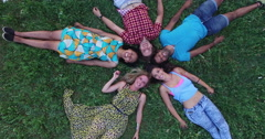 Aerial of group of friends forming a star shape lying in grass - stock footage
