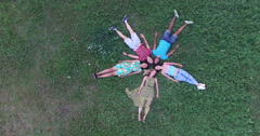 Young happy friends forming a star shape lying in grass - stock footage