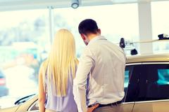 Couple buying car in auto show or salon Kuvituskuvat