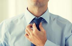 Stock Photo of close up of man in shirt adjusting tie on neck